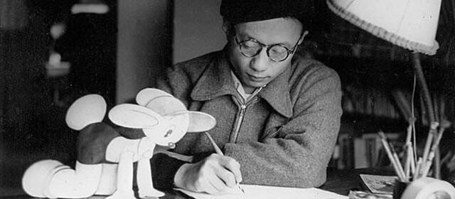 Osamu Tezuka at work accompanied by a cartoon animal