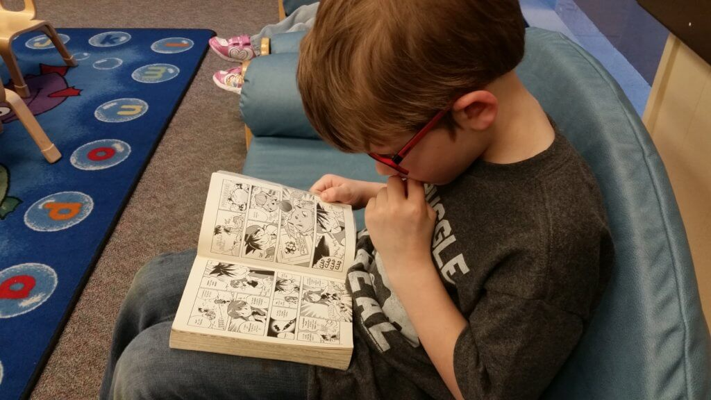 My son reading a Pokemon manga