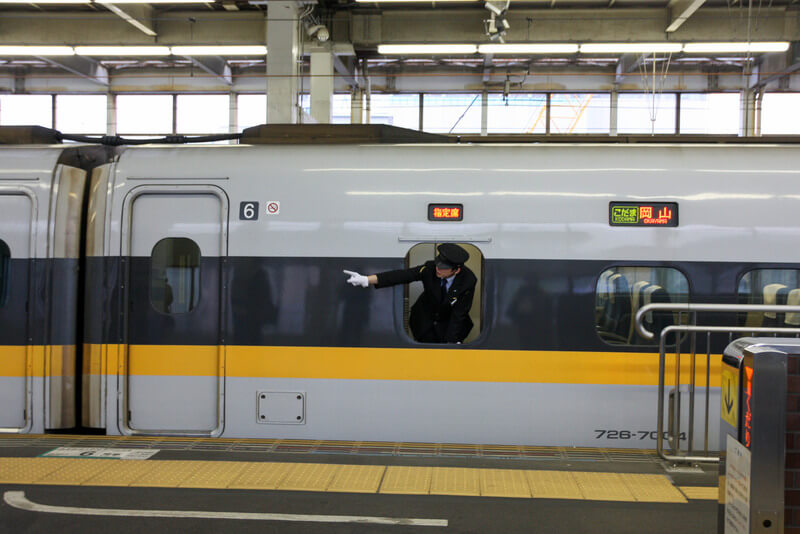 A Hiroshima train conductor pointing along the track