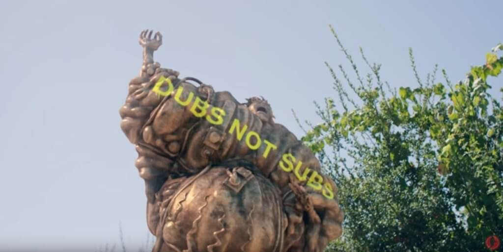 "A screenshot of a statue with ""Dubs not subs"" written in graffiti"