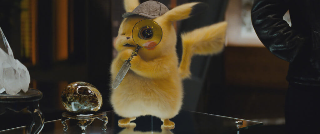 Pikachu looking through a magnifying glass