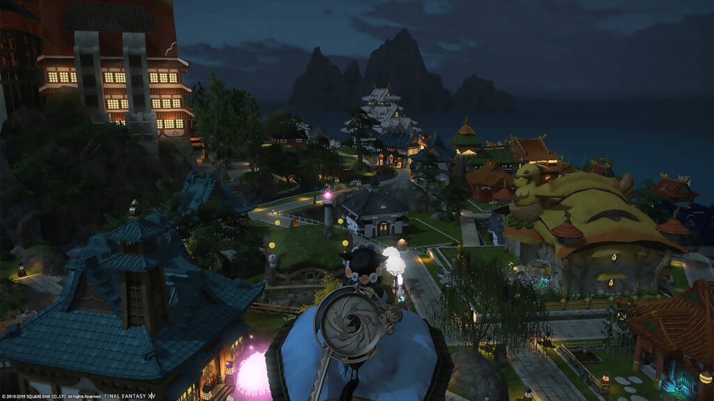 Player is standing in a high place looking down at the Shirogane Housing during night hours.
