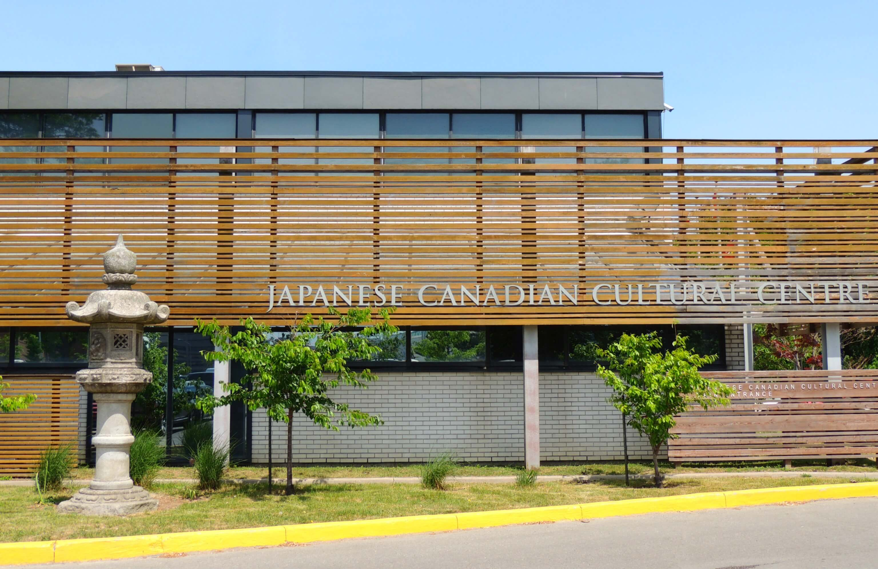 Exterior of the Japanese Canadian Culture Center in Toronto with a Japanese stone statue at the front of the building.