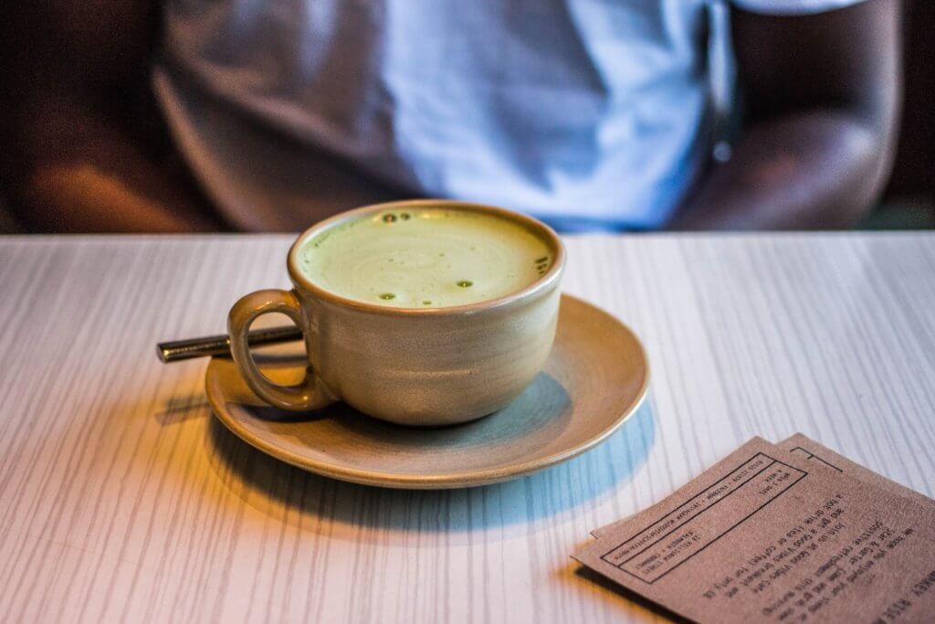 A person sitting in a cafe with a cup of matcha tea in front of them with the cafe menu next to the cup