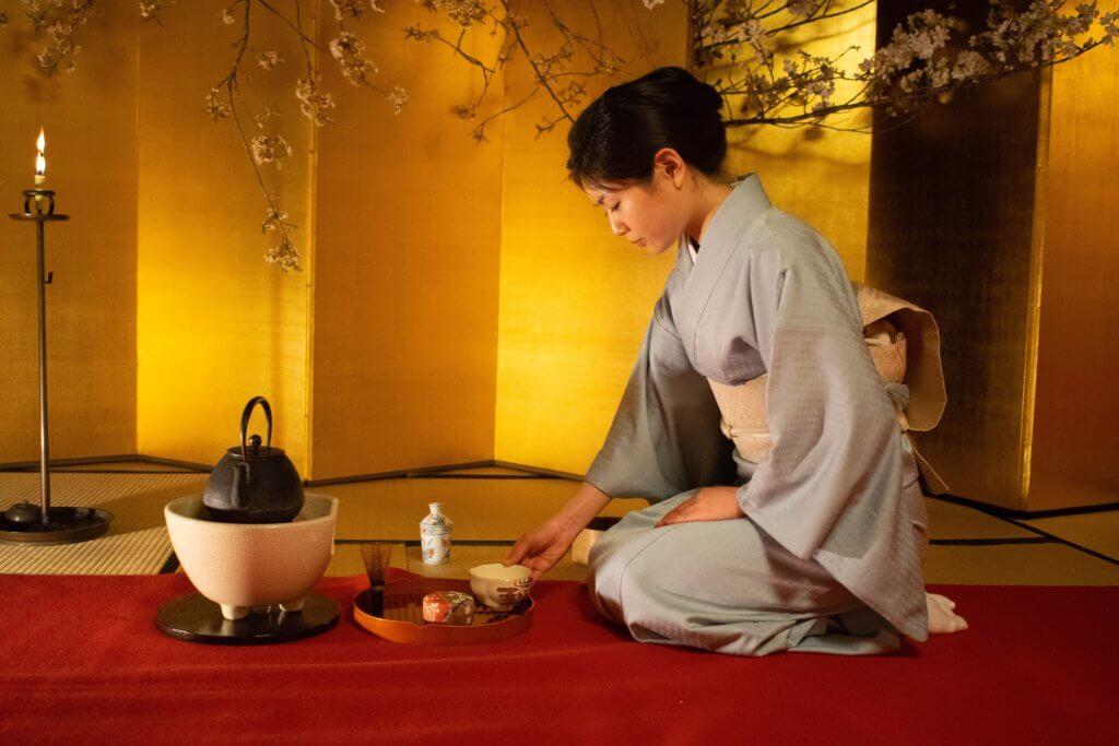 Woman kneeling and performing a tea ceremony
